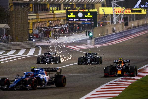 Esteban Ocon, Alpine A521, leads Sergio Perez, Red Bull Racing RB16B, Sebastian Vettel, Aston Martin AMR21, and Yuki Tsunoda, AlphaTauri AT02, as sparks fly