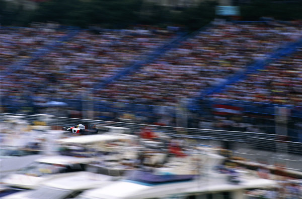 Ayrton Senna, McLaren MP4-7A Honda, at speed between the grandstands and the yachts.