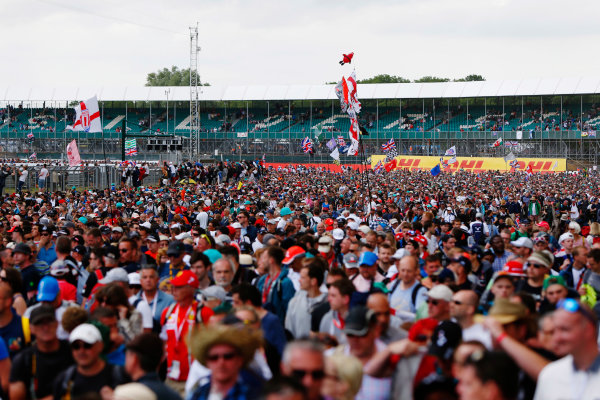 Silverstone, Northamptonshire, England. Sunday 5 July 2015. Fans invade the circuit after the race to see the podium celebrations. World Copyright: Zak Mauger/LAT Photographic. ref: Digital Image _L0U6633