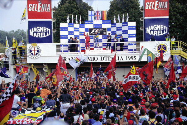 Fans gather in front of the podium as Johnny Herbert celebrates victory with Mika Hakkinen, 2nd position, and Heinz-Harald Frentzen, 3rd position.