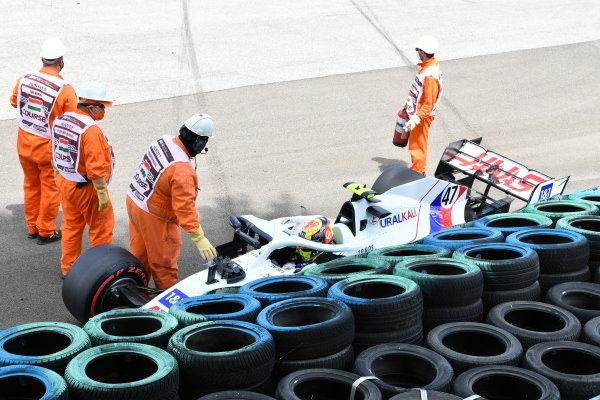 Marshals assist Mick Schumacher, Haas VF-21, after a crash in FP3