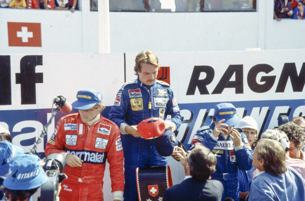 Keke Rosberg, 1st position, Alain Prost, 2nd position, and Niki Lauda, 3rd position, on the podium.