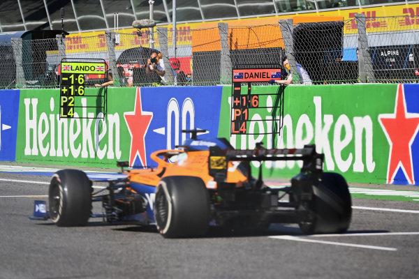 Daniel Ricciardo, McLaren MCL35M, passes his pit board
