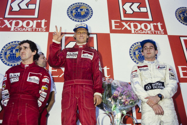 Niki Lauda, newly-crowned world champion by finishing in 2nd position, stands atop of the podium alongside Alain Prost, 1st position, and Ayrton Senna, 3rd position. Ron Dennis can be seen behind Prost.