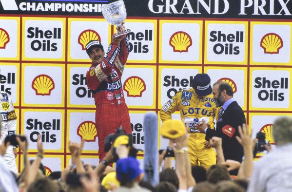 Nigel Mansell, 1st position, celebrates on the podium. Prince Michael of Kent talks to Ayrton Senna, 3rd position.