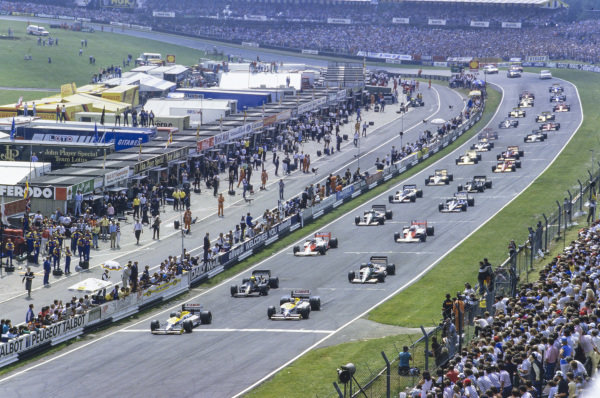 Nelson Piquet, Williams FW11 Honda, pulls away from Nigel Mansell, Williams FW11 Honda, Ayrton Senna, Lotus 98T Renault, and Gerhard Berger, Benetton B186 BMW, at the start.