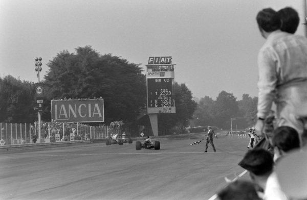 Denny Hulme, McLaren M7A Ford, takes the chequered flag for victory.