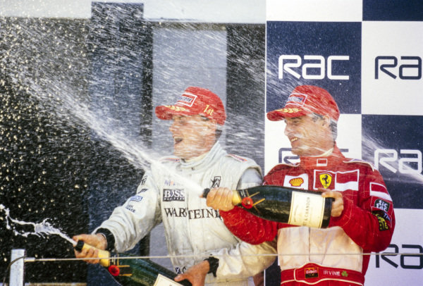 David Coulthard, 1st position, and Eddie Irvine, 2nd position, spray champagne on the podium.