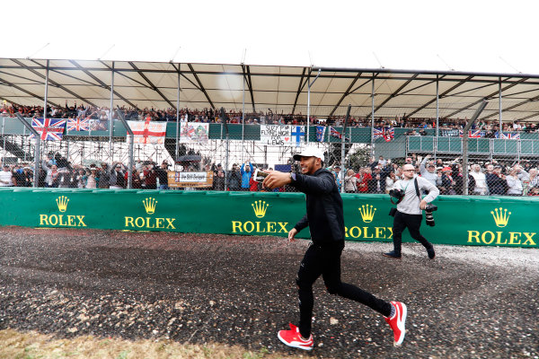 Silverstone, Northamptonshire, UK.  Thursday 13 July 2017. Lewis Hamilton, Mercedes AMG, runs past fans in a grandstand while filming them on his phone. World Copyright: Glenn Dunbar/LAT Images  ref: Digital Image _X4I2512