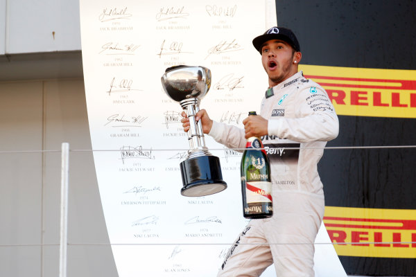 Suzuka Circuit, Suzuka, Japan. Sunday 27 September 2015. Lewis Hamilton, Mercedes AMG, 1st Position, with his trophy and Champagne on the podium. World Copyright: Alastair Staley/LAT Photographic. ref: Digital Image _R6T2645