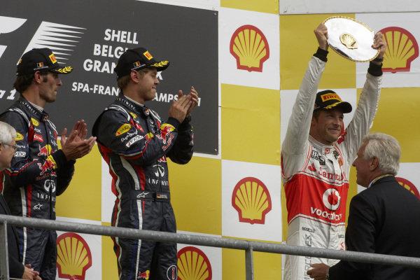 Jenson Button, 3rd position, celebrates on the podium alongside Sebastian Vettel, 1st position, and Mark Webber, 2nd position.