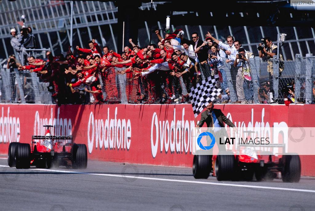 2002 Italian Grand PrixMonza, Italy. 14th - 16th September 2002Rubens Barrichello, Ferrari F2002, and Michael Schumacher, Ferrari F2002, cross the finish line narrowly missing flag waver.World Copyright - LAT Photographicref: 35mm Transparency 02_ITA_27
