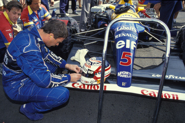 Nigel Mansell puts some tape on his helmet on the grid.
