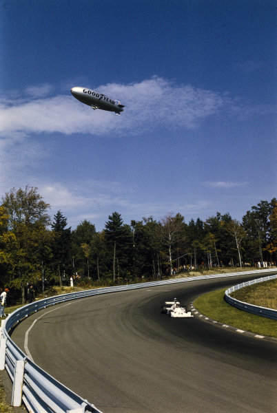 James Hunt, Hesketh 308 Ford drives beneath the Goodyear blimp.