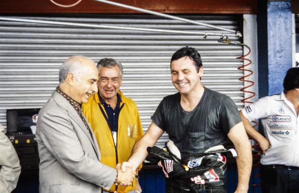 Alan Jones shakes hands with Juan Manuel Fangio.