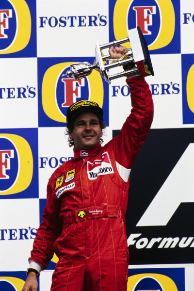 Gerhard Berger, 2nd position, holds his trophy aloft on the podium.