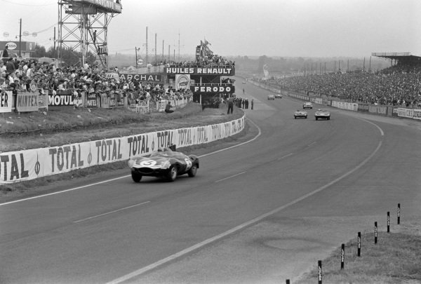 "Innes Ireland / Masten Gregory, Ecurie Ecosse, Jaguar D-type ""Modified""-Jaguar XK, leads Ron Flockhart / John Lawrence, Ecurie Ecosse, Tojeiro-Jaguar XK, and Graham Hill / Derek Jolly, Team Lotus Engineering, Lotus Mk 15-Coventry Climax FPF."