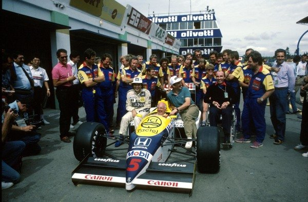 (L to R) Nelson Piquet (BRA) Williams FW11, Murray Walker (GBR), Nigel Mansell (GBR) Williams FW11, Team Owner Frank Williams and the Williams Team pose for a photograph.