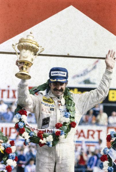 Clay Regazzoni celebrates victory on the podium with his trophy.