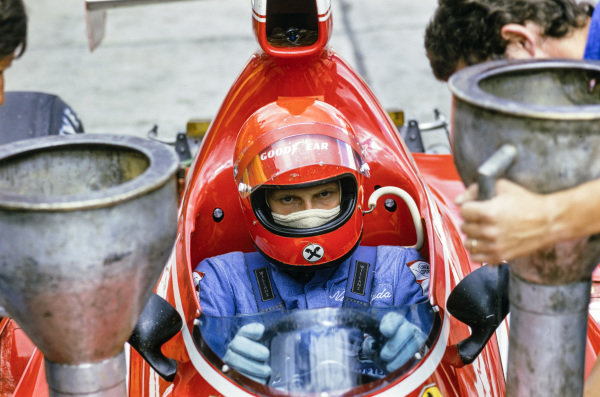 Niki Lauda waits in the pits as his Ferrari 312B3 is fuelled.