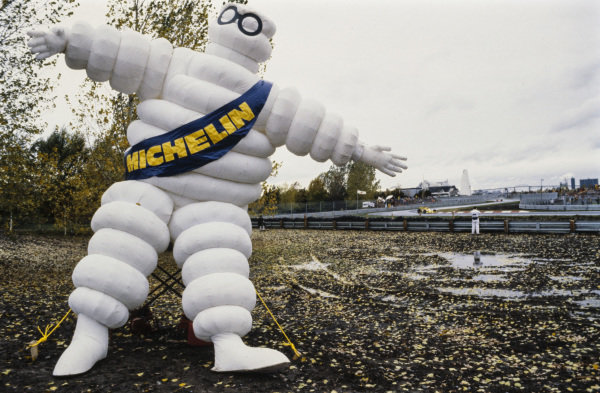 The Michelin Man stands trackside as Jean-Pierre Jabouille, Renault RS01 passes by in the background.
