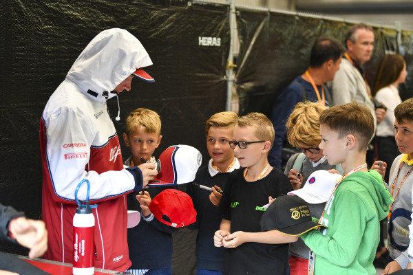 Kimi Raikkonen, Alfa Romeo Racing, signs autographs for kids