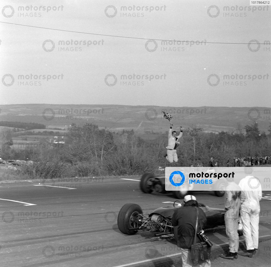 Graham Hill, BRM P261, crosses the finish line and takes the chequered flag.
