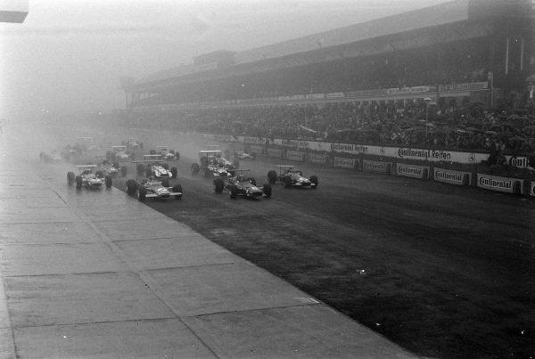 Chris Amon, Ferrari 312, leads Graham Hill, Lotus 49B Ford, and Jochen Rindt, Brabham BT26 Repco, at the start.