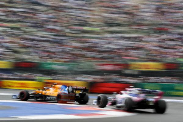 Carlos Sainz Jr., McLaren MCL34, leads Sergio Perez, Racing Point RP19