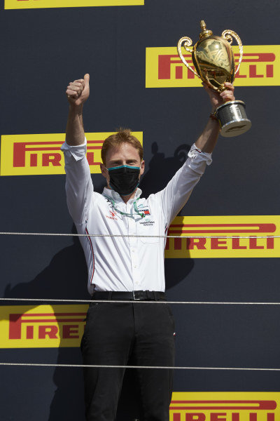 The Mercedes constructors' winner representative celebrates on the podium and holds his trophy
