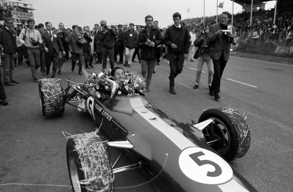 Race winner Jim Clark arrives in the pit lane in his Lotus 49 Ford. His tyres are covered in hay.