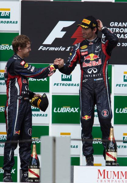 Interlagos, Sao Paulo, Brazil. 27th November 2011. Sebastian Vettel, Red Bull Racing RB7 Renault, 2nd position, congratulates Mark Webber, Red Bull Racing RB7 Renault, 1st position, on the podium. Portrait. Podium.  World Copyright: Steve Etherington/LAT Photographic ref: Digital Image SNE28309