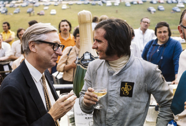 Emerson Fittipaldi enjoys a glass of champagne. Fittipaldi received 100 bottles for setting the fastest time on Thursday practice. The Evening News presented the prize.