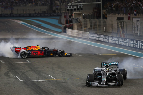 Lewis Hamilton, Mercedes AMG F1 W10, 1st position, and Max Verstappen, Red Bull Racing RB15, 2nd position, perform donuts on the grid in celebration at the end of the race