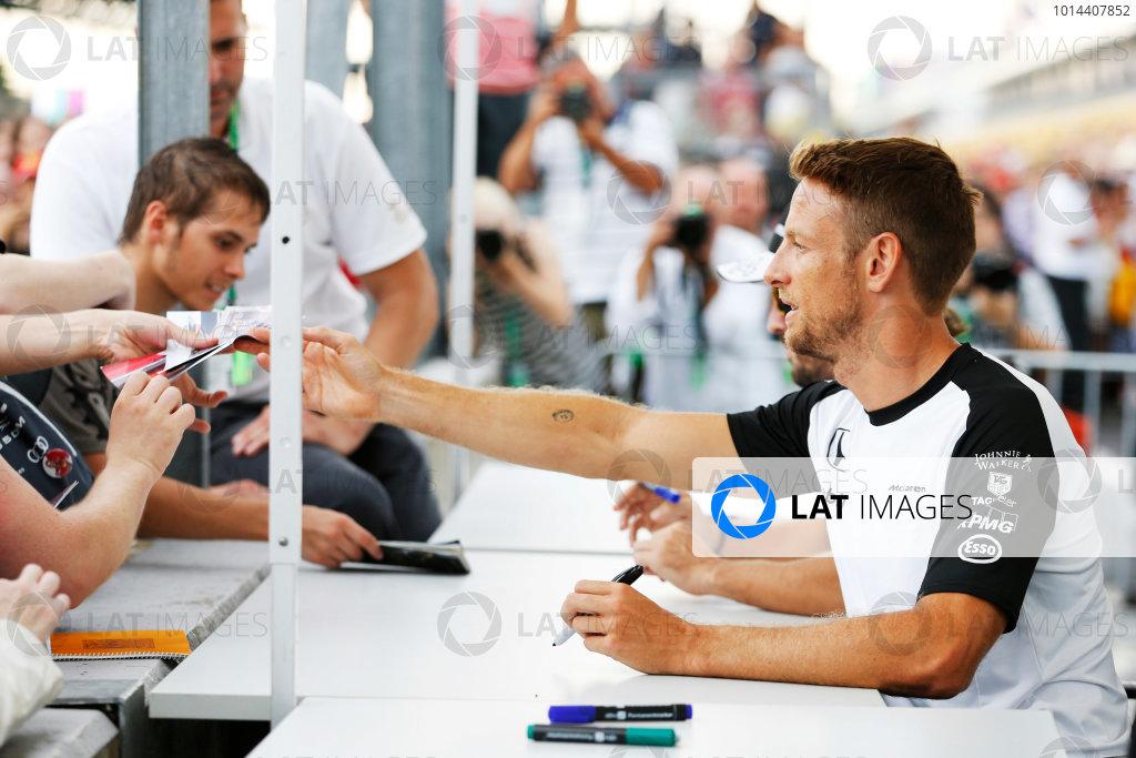 Hungaroring, Budapest, Hungary. Thursday 23 July 2015. Jenson Button, McLaren, signs autographs for fans.  World Copyright: Charles Coates/LAT Photographic ref: Digital Image _J5R0974