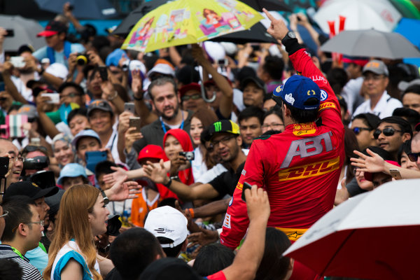 2015/2016 FIA Formula E Championship. Putrajaya ePrix, Putrajaya, Malaysia. Saturday 7 November 2015. Podium Lucas Di Grassi (BRA), ABT Audi Sport FE01 runs through the crowd at the podium Photo: Sam Bloxham/FIA Formula E/LAT ref: Digital Image _SBL1248