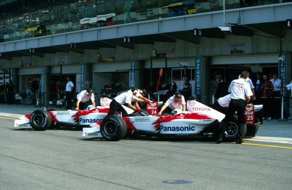 Allan McNish (GBR), foreground, and Toyota team mate Mika Salo (FIN), have their TF102s pushed back into their pit garages in formation.