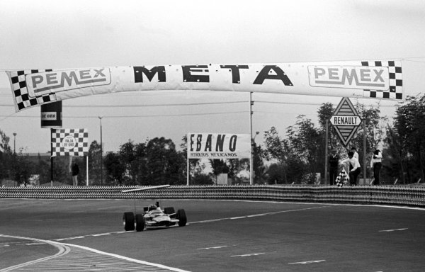 Graham Hill (GBR) Lotus 49B crosses the finish line to take race victory and clinch his second World Championship. Mexican Grand Prix, Mexico City, 3 November 1968.