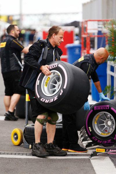 A Pirelli employee manhandles a wheel in the paddock.