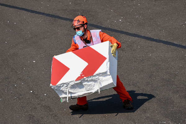 Marshal's piece together broken barrier after Sebastian Vettel, Ferrari SF1000 collided with it