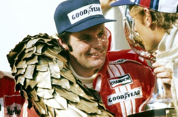 (L to R): Alan Jones (AUS) Shadow celebrates on the podium with Hans-Joachim Stuck (GER) Brabham after claming his and Shadow's first victory. Austrian Grand Prix, Rd 12, Osterreichring, Austria, 14 August 1977.