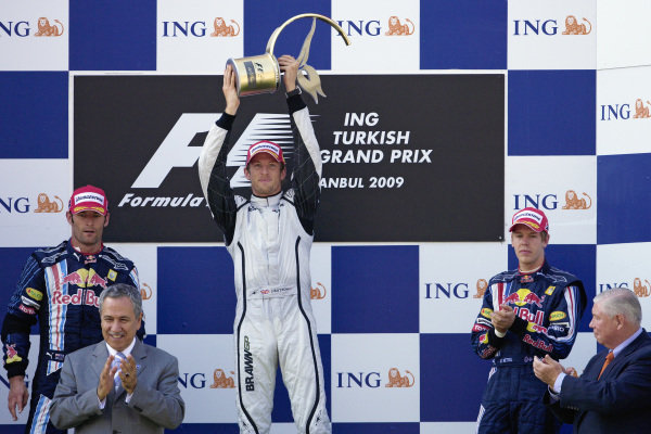 Jenson Button celebrates victory on the podium with Mark Webber, 2nd postion, and Sebastian Vettel, 3rd position.