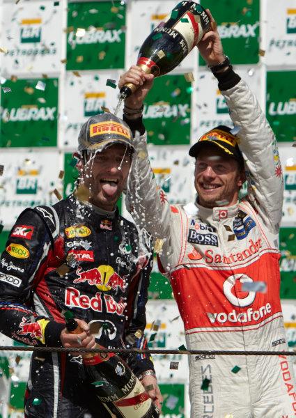 Interlagos, Sao Paulo, Brazil. 27th November 2011. Jenson Button, McLaren MP4-26 Mercedes, 3rd position, gives Mark Webber, Red Bull Racing RB7 Renault, 1st position, a soaking on the podium. Portrait. Podium.  World Copyright: Steve Etherington/LAT Photographic ref: Digital Image SNE28386