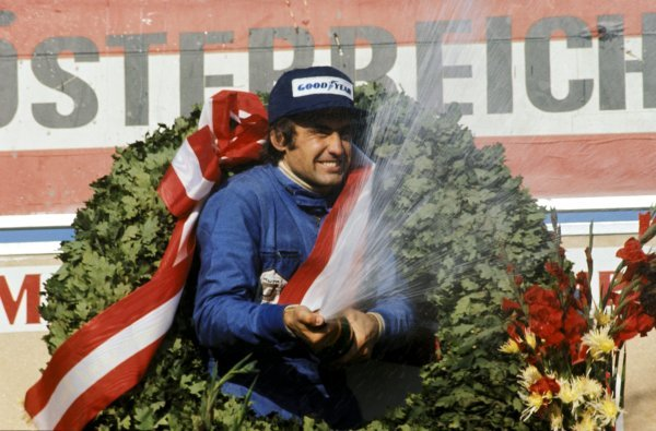 Carlos Reutemann (ARG) Brabham celebrates his victory on the podium. Austrian Grand Prix, Osterreichring, 18 August 1974. BEST IMAGE