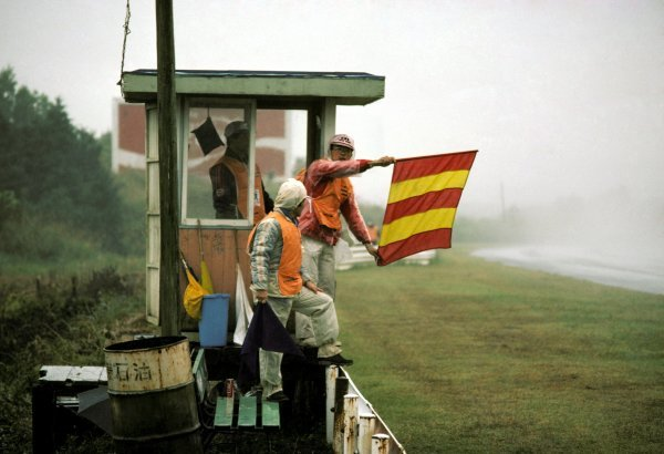 A trackside marshal holds out the red and yellow striped flag, warning drivers that there was water on the track. The race was nearly cancelled because of the appalling wet conditions.