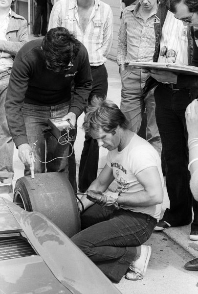 Michelin tyre technicians check the temperature and air pressure of a tyre on a Ferrari 312T3 in the pits.