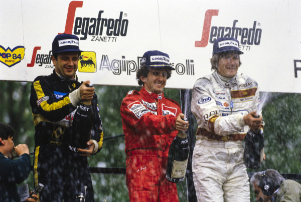 Alain Prost, 1st position but later disqualified, celebrates on the podium alongside Elio de Angelis, 1st position, and Thierry Boutsen, 2nd position.