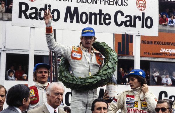 Jean-Pierre Jabouille celebrates victory on the podium with Gilles Villeneuve, 2nd position, and René Arnoux, 3rd position.