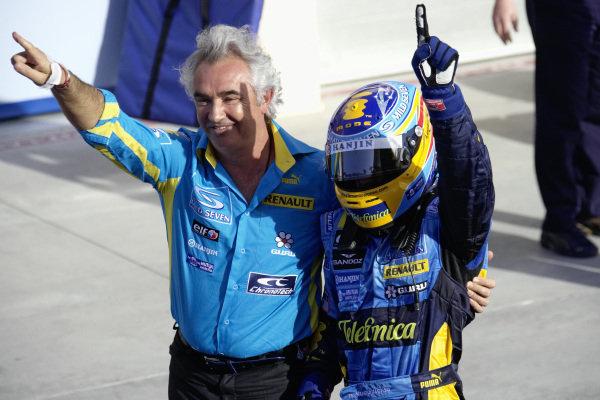 Flavio Briatore and Fernando Alonso celebrate victory in parc fermé.