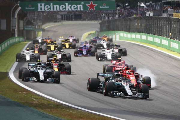Lewis Hamilton, Mercedes AMG F1 W09, leads a locked-up Sebastian Vettel, Ferrari SF71H, Valtteri Bottas, Mercedes AMG F1 W09, Kimi Raikkonen, Ferrari SF71H, Max Verstappen, Red Bull Racing RB14 Tag Heuer, and the rest of the field at the start.